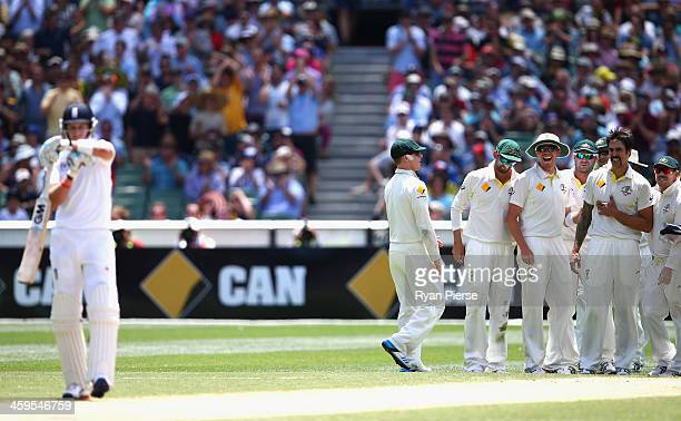 Joe Root of England reviews his caught behind decision off the bowling of Mitchell Johnson of Australia as the Australian Team look on during day...
