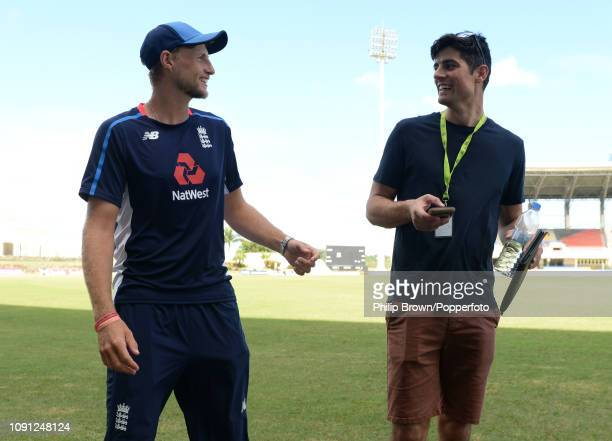 Joe Root of England speaks to Sir Alastair Cook before a training session at the Sir Vivian Richards Stadium before the second Test match between the...