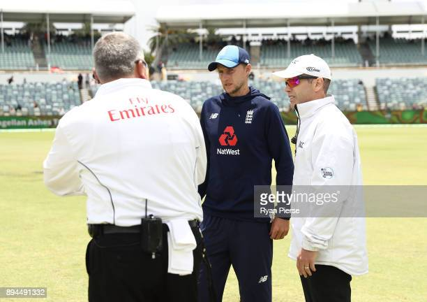 Joe Root of England speaks with the umpires as groundsmen dry the pitch after rain delayed the start of play during day five of the Third Test match...