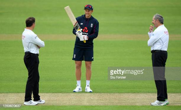 Joe Root of England talks to umpires Richard Kettleborough and Richard Illingworth prior to Day One of a England Warm Up Match at the Ageas Bowl on...