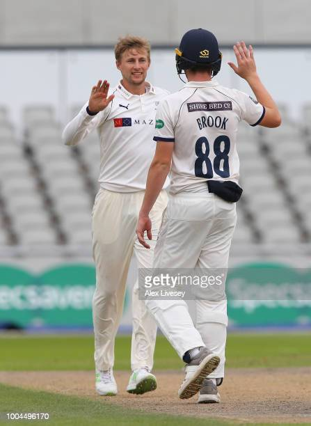 Joe Root of Yorkshire celebrates with Harry Brook after taking the wicket of Matt Parkinson of Lancashire during the Specsavers Championship Division...