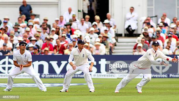 Joe Root takes a catch to dismiss Chris Rogers of Australia as Alastair Cook and Ian Bell of England look on during day two of the 4th Investec Ashes...