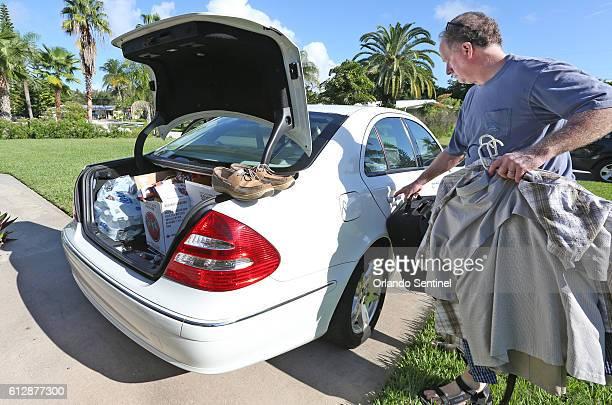 Joe Roth of Cocoa Beach Fla packs his family's car on Wednesday Oct 5 2016 as he and his wife Debi prepare to evacuate as Hurricane Matthew...