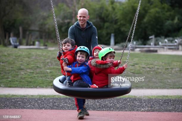 Joe Ruddock pushes Ethan Ruddock Callum Jackson Caleb ruddock and Sam Jackson on a swing at the Victoria Park playground on March 6, 2021 in London,...