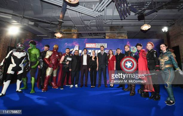 Joe Russo, Paul Rudd, Scarlett Johansson, Chris Hemsworth, Trinh Tran and Anthony Russo pose with Marvel characters as they attend the UK Fan Event...