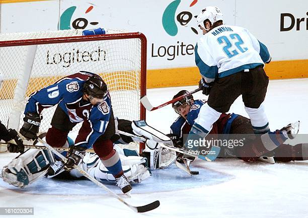 Joe Sakic and Alex Tanguay get the puck close to San Jose goalie Evgeni Nabokov and Scott Hannan #22 during first period of play Monday evening at...