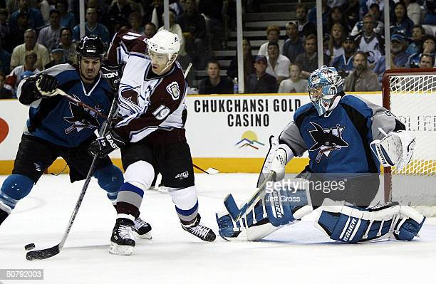 Joe Sakic of the Colorado Avalanche is checked from behind by Scott Hannan of the San Jose Sharks while trying to score on San Jose goaltender Evgeni...