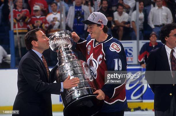 Joe Sakic of the Colorado Avalanche takes the Stanley Cup from NHL commissioner Gary Bettman after the Avalanche defeated the Florida Panthers in...
