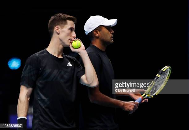 Joe Salisbury of Great Britain and Rajeev Ram of The United States speak to each other during their round robin doubles match against Lukasz Kubot of...