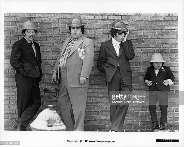 Joe Santos Irving Selbst Jerry Orbach and Herve Villechaize standing against a brick wall in a scene from the film 'The Gang That Couldn't Shoot...