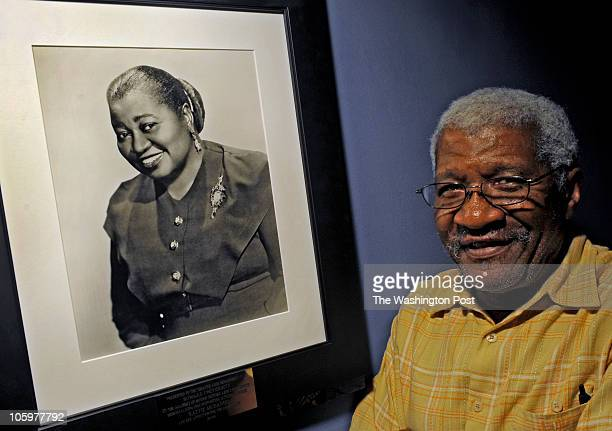 Joe Selmon Chairman Theatre Arts Department Howard University stands next to a photograph of Hattie McDaniel the first African American to win an...