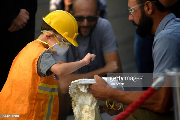 Joe Sertich curator of dinosaurs holds a piece of the casing for 3 year old Cooper Richards to check the hardness at the Denver Museum of Nature...