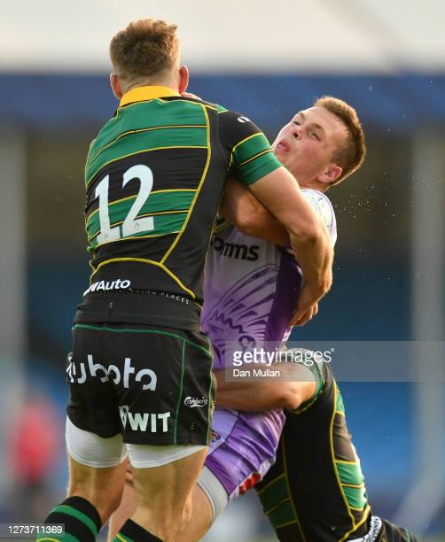 Joe Simmonds of Exeter Chiefs is tackled by Rory Hutchinson and Henry Taylor of Northampton Saints during the Heineken Champions Cup Quarter Final...