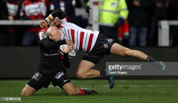 Joe Simpson of Gloucester dives over for the first try despite being held by Thomas Ramos during the Heineken Champions Cup Round 1 match between...