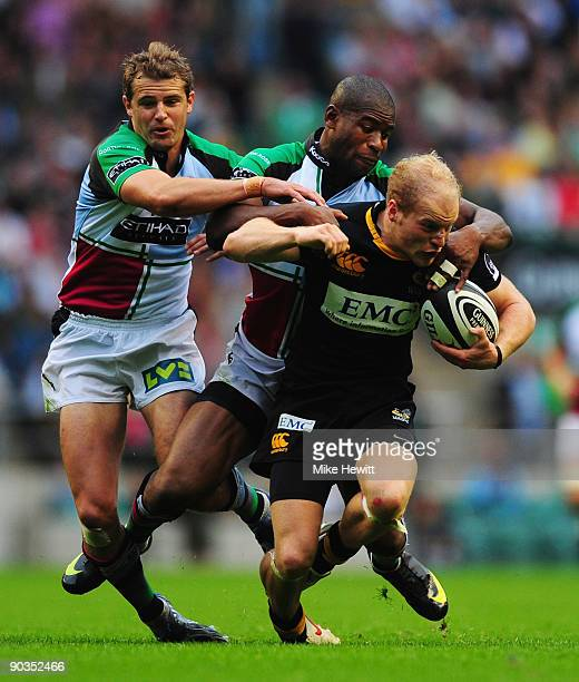 Joe Simpson of Wasps is stopped by Ugo Monye and Nick Evans of Harlequins during the Guinness Premiership match between London Wasps and Harlequins...