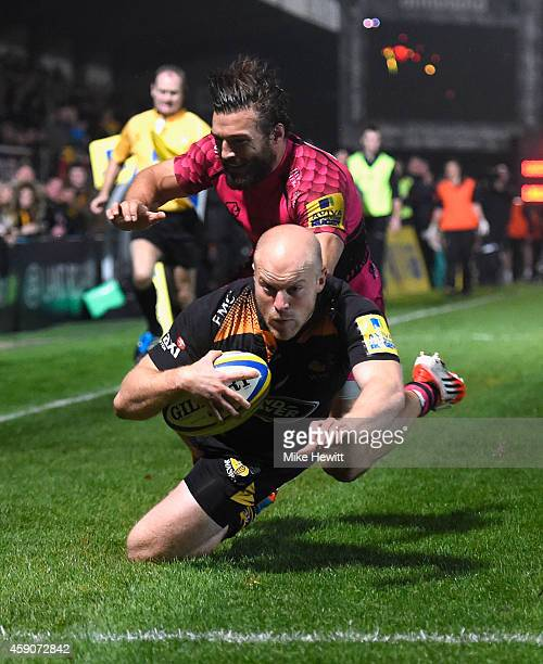 Joe Simpson of Wasps scores a try despite the efforts of Seb Segmann of London Welsh during the Aviva Premiership match between Wasps and London...