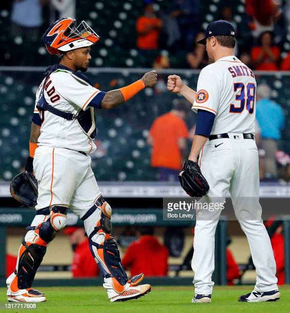 Joe Smith of the Houston Astros bumps fists with Martin Maldonado after defeating the Los Angeles Angels 9-1 at Minute Maid Park on May 12, 2021 in...