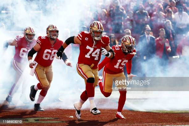 Joe Staley and Deebo Samuel of the San Francisco 49ers run out of the tunnel prior to the NFC Divisional Round Playoff game against the Minnesota...
