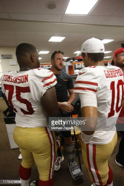 Joe Staley of the San Francisco 49ers talks with Laken Tomlinson and Jimmy Garoppolo in the locker room following the game against the Cincinnati...