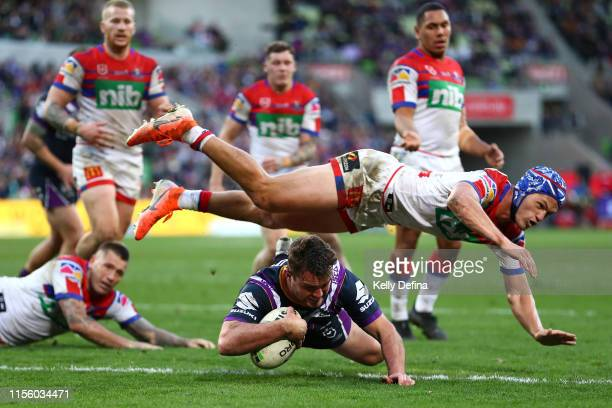 Joe Stimson of the Storm scores a try as Kalyn Ponga of the Knights defends during the round 14 NRL match between the Melbourne Storm and the...