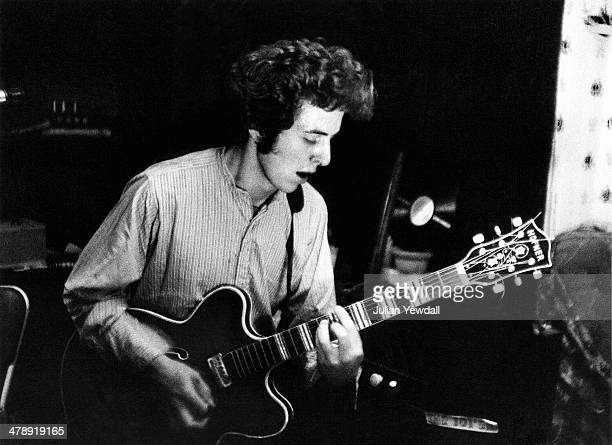 Joe Strummer , of English pub rock group The 101ers, playing a Hofner Verythin guitar in the basement rehearsal room at the band's squat at 101...