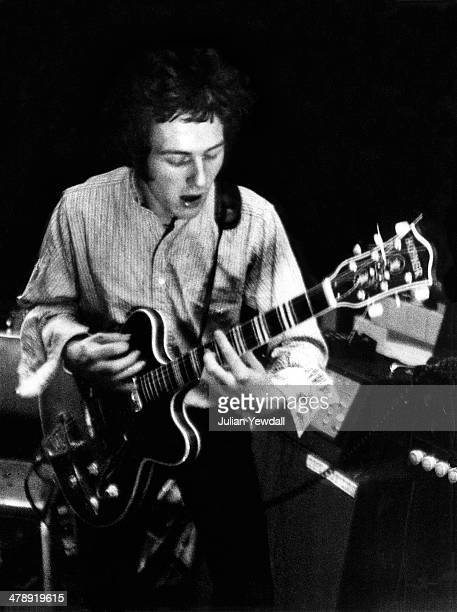Joe Strummer of English pub rock group The 101ers playing a Hofner Verythin guitar in the basement rehearsal room at the band's squat at 101...