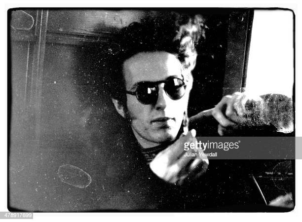 Joe Strummer of English pub rock group The 101ers repairs a badly burning hash joint 1975