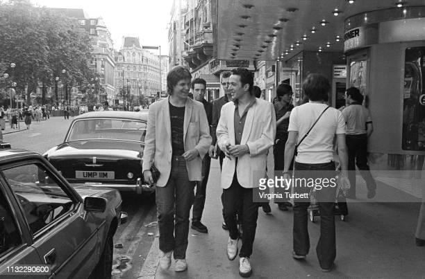 Joe Strummer of The Clash talks to 'Sounds' music journalist Dave McCullough with Mick Jones and Paul Simonon behind, Leicester Square, London, 6th...