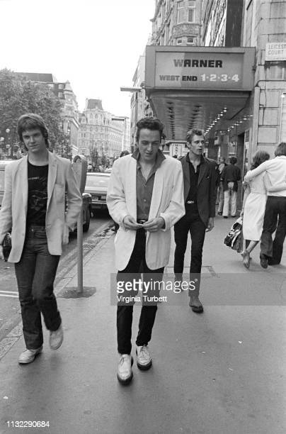 Joe Strummer of The Clash talks to 'Sounds' music journalist Dave McCullough with Paul Simonon behind, Leicester Square, London, 6th July 1979.