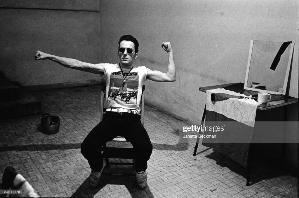 Joe Strummer (1952 - 2002) of the punk rock group The Clash, strikes a warrior pose in his dressing room in Milan, Italy. 1981.