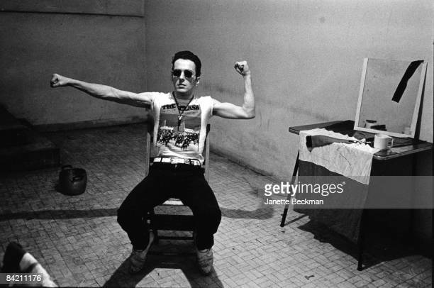 Joe Strummer of the punk rock group The Clash strikes a warrior pose in his dressing room in Milan Italy 1981