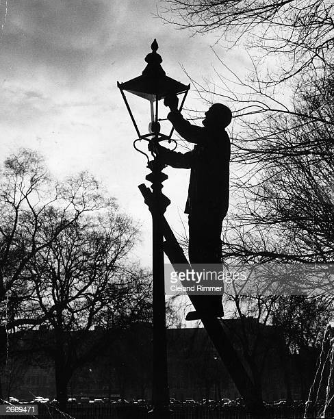 Joe Styles from Putney, London who has a been a lamp lighter for 40 years, cleaning a lantern in Hyde Park, London. He has 183 gas lamps in his care.