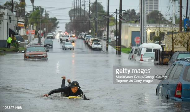 Joe Suzuki paddles around submerged cars on Pomona Avenue near 17th Street in Costa Mesa CA on Thursday Dec 6 2018 Heavy rain from a winter storm...