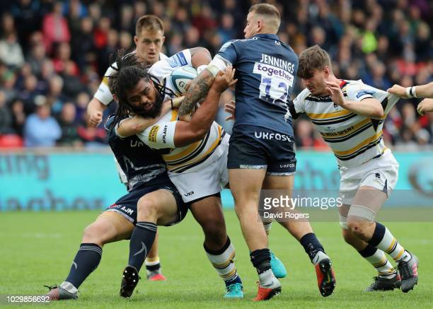 Joe Taufete'e of Worcester Warriors is held by Mark Jennings and AJ MacGinty during the Gallagher Premiership Rugby match between Sale Sharks and...