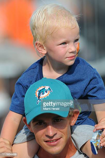 Joe Terry and his son Joey enjoy the sights during Miami Dolphins' practice at the team's training facility at Nova Southeastern University in Davie,...