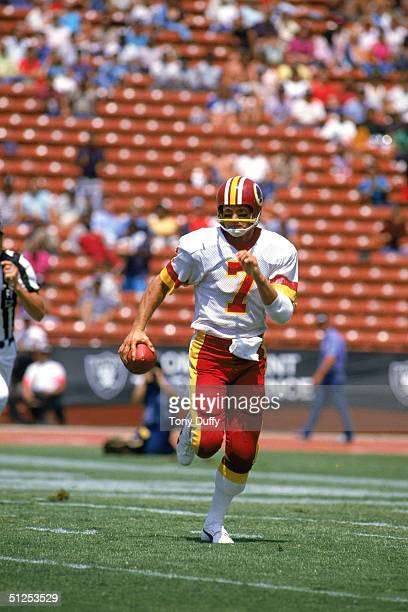 Joe Theismann of the Washington Redskins moves as he looks to pass during a 1983 NFL season game against the Los Angeles Raiders at Los Angeles...