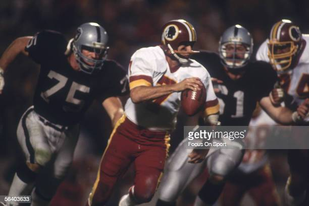 Joe Theismann of the Washington Redskins scrambles to avoid two rushing Oakland Raiders' Howie Long and teammate during Super Bowl XVIII against the...