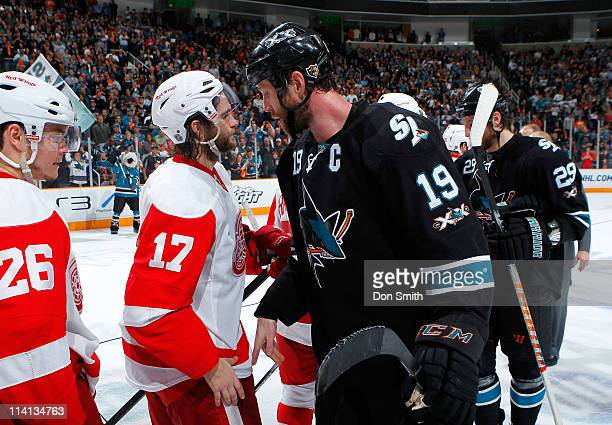 Joe Thornton and Ryane Clowe of the San Jose Sharks partake in the postgame handshakes after a victory against Patrick Eaves and Jiri Hudler of the...