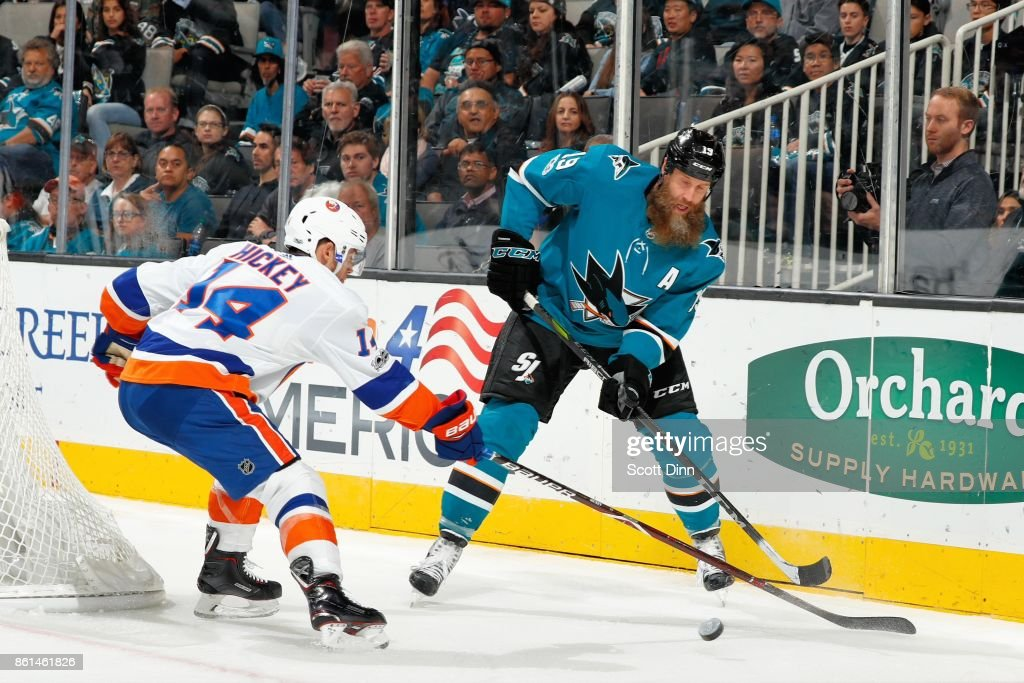 Joe Thornton #19 of the San Jose Sharks and Thomas Hickey #14 of the New York Islanders battle for the puck at SAP Center on October 14, 2017 in San Jose, California.