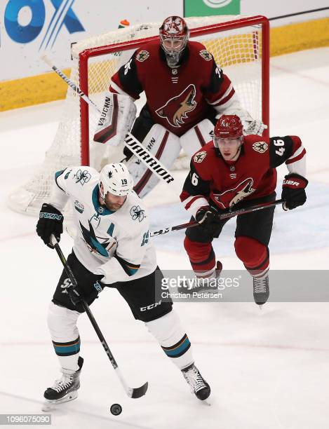 Joe Thornton of the San Jose Sharks controls the puck ahead of Ilya Lyubushkin and goaltender Darcy Kuemper of the Arizona Coyotes during the first...