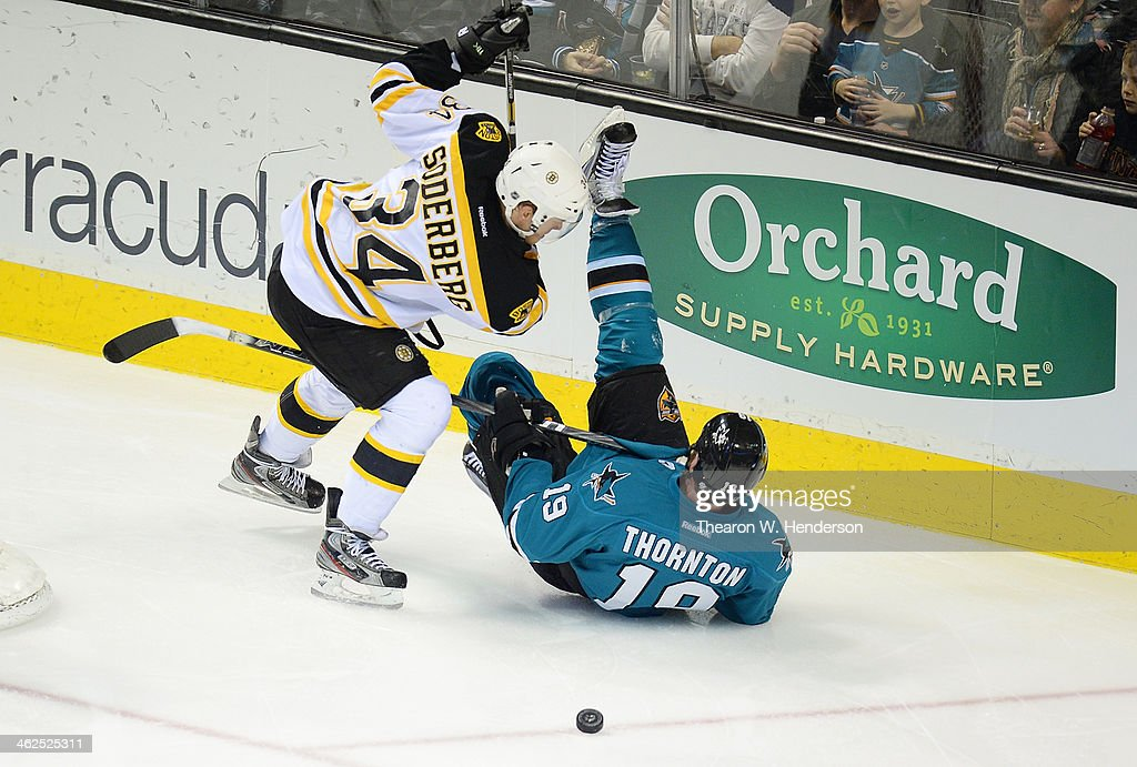 Joe Thornton #19 of the San Jose Sharks hits the ice on his back after colliding with Carl Soderberg #34 of the Boston Bruins during the third period at SAP Center on January 11, 2014 in San Jose, California.