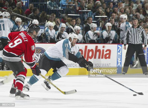 Joe Thornton of the San Jose Sharks, in his first game with the Sharks, reaches for the puck against Tim Connolly of the Buffalo Sabres on December...