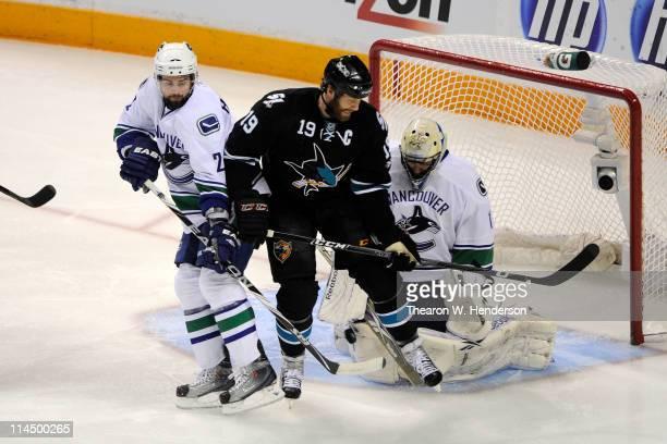 Joe Thornton of the San Jose Sharks screens goaltender Roberto Luongo of the Vancouver Canucks as Dan Hamhuis of the Vancouver Canucks defends the...