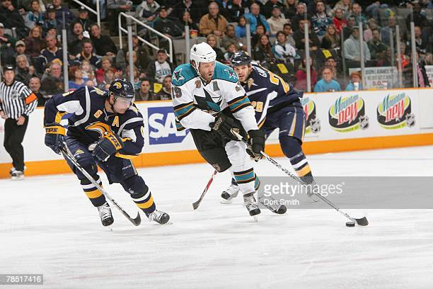 Joe Thornton of the San Jose Sharks skates by Paul Gaustad and Jaroslav Spacek of the Buffalo Sabres during an NHL game on December 8 2007 at HP...