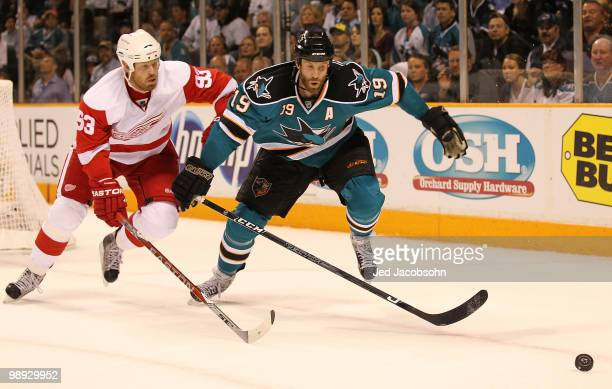 Joe Thornton of the San Jose Sharks skates with the puck against Johan Franzen of the Detroit Red Wings in Game Five of the Western Conference...