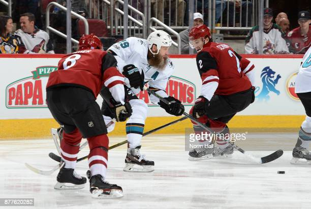 Joe Thornton of the San Jose Sharks skates with the puck between Tobias Rieder and Luke Schenn of the Arizona Coyotes during the first period at Gila...