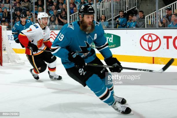 Joe Thornton of the San Jose Sharks stays ahead of TJ Brodie of the Calgary Flames at SAP Center on December 28 2017 in San Jose California