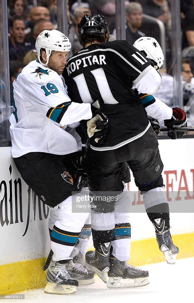 Joe Thornton #19 of the San Jose Sharks takes a check from Anze Kopitar #11 of the Los Angeles KiBobby Knoop #1 of the Los Angeles Angels in Game Six of the First Round of the 2014 NHL Stanley Cup Playoffs at Staples Center on April 28, 2014 in Los Angeles, California.