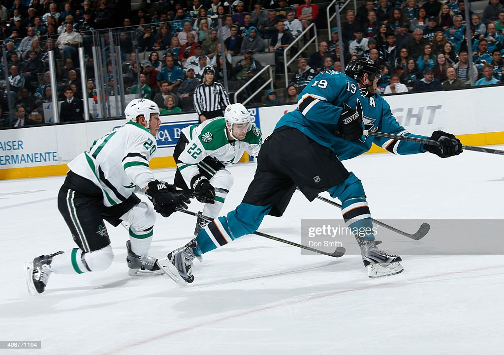 Joe Thornton #19 of the San Jose Sharks takes a shot on net against Cody Eakin #20 and Colton Sceviour #22 of the Dallas Stars at the SAP Center on April 6, 2015 in San Jose, California .
