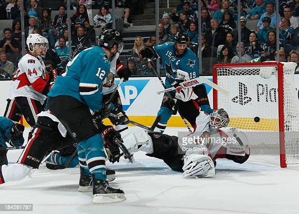 Joe Thornton of the San Jose Sharks watches as Patrick Marleau scores a goal against Robin Lehner of the Ottawa Senators during an NHL game on...
